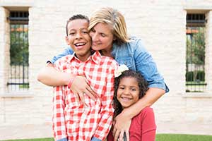 A mother embraces her children, identifying herself as their source of strength in the journey.
